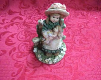 Vintage little girl sitting on a bench holding a baby doll figurine