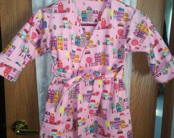 Girls 3T double layered flannel robe in pink flannel novelty print. Calf length. Snap top. Sash tie.