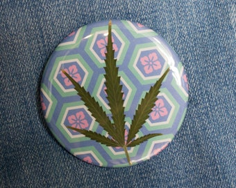 Pressed Cannabis Leaf Button on Blue, Turquoise & Pink Background