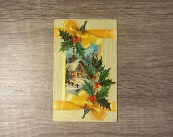 Vintage Merry Christmas  1910s postcard feat. a snowy home with a holly and yellow ribbon border, no postage, no postmark