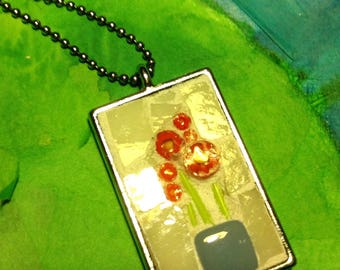 Orange flowers in case with off white background rectangle mosaic pendant