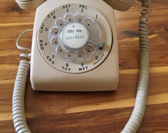 Vintage beige rotary telephone. Working landline phone. Decorative accent for vintage room. Dial phone