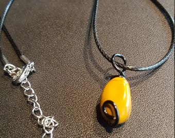 Yellow stone pendant on a black cord necklace