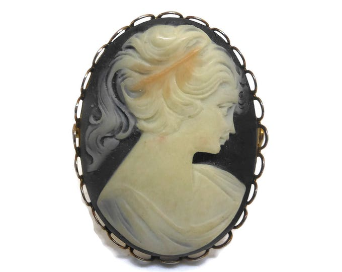 Mid Century cameo, hand carved black background, cream colored woman, scalloped gold edging