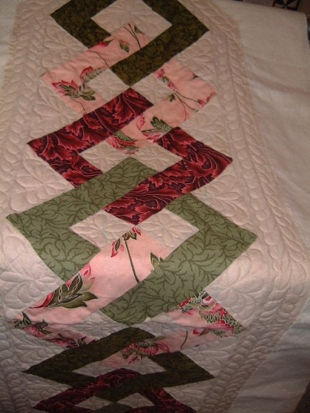 Heres a little table runner I practiced feathers on.