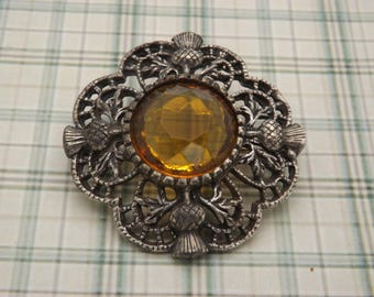 A lovely  Scottish / Celtic vintage jewelry brooch made in a round thistle design using antique silvertone metal with amber faceted stone