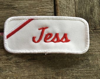 "Jess. A white work shirt name patch that says ""Jess"" in red script with white border"