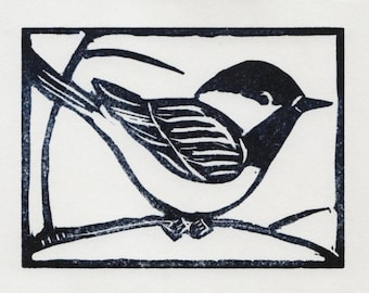 An original linocut print of a black-capped chickadee