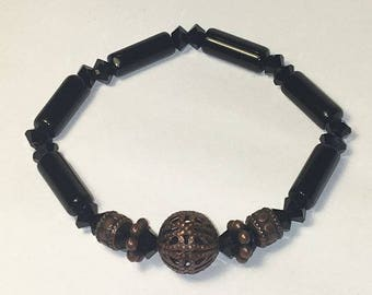 Black stretch bracelet with brown centerpiece and accent beads. Stretchy One Size