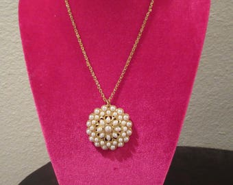 Lovely vintage faux pearl and gold tone pendant and necklace chain. Round pendant measures approx 1 3/4 inch in diameter. Adjustable chain.