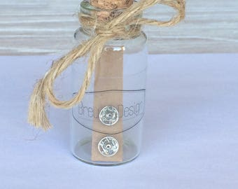 Tiny Popper Stud Earrings, displayed in glass bottle