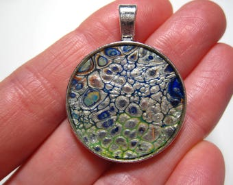 Silver with dark blue and green acrylic pour pendant - Musculair