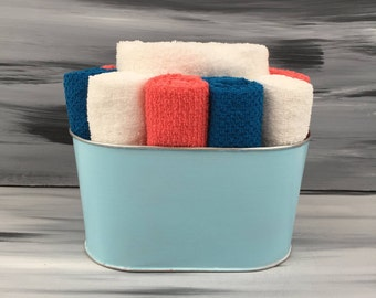 Light Blue Bathroom Towel/Wash Cloth BIn with 1 white hand towel, 3 teal wash cloths,  3 orange wash cloths and 3 white wash cloths.