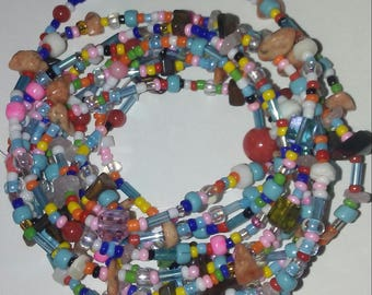 "Multi Wrap Bracelet with Seed, Glass, Shell, Fossil, Gem Chips and Crystal Beads. Aprox. 70"" on Strong Nylon with Closure."