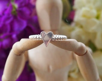 An cute dainty sterling silver hand cut heart stacking ring on a band of sterling silver balls...