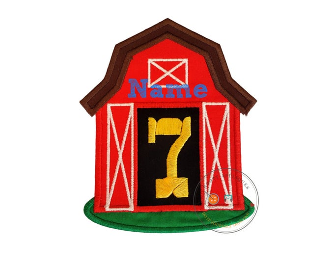 Big, red barn iron on applique with large, birthday number 7 (seven) in yellow on a black background between two white detailed doors.