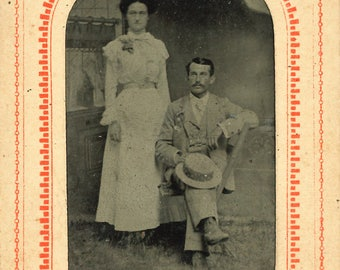 Tintype of couple in paper frame / Cartouche, man holds a straw hat