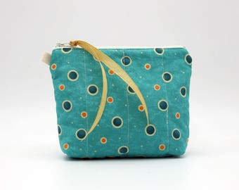 Turquoise cosmetic bag with blue and orange dots