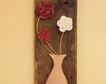 Three metal flowers in a faux copper vase on recycled wood.