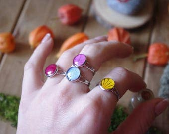 Bright colored rings with petals of flowers in resin