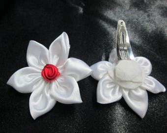 Adorned with a white satin flower with a hair clip is adorned with a red rose