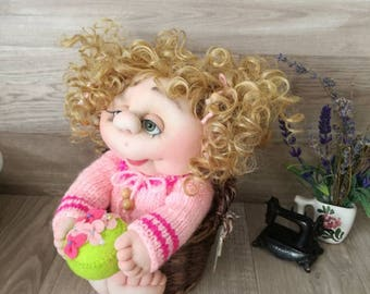 Handmade doll from textiles with curly blonde hair pink sweater