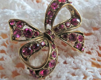 Vintage fuschia pink crystal bow brooch signed LC..Liz Clairborne
