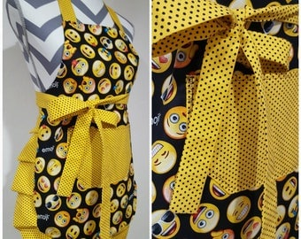 Youth apron. Girl's apron. Emoji faces on main bodice. Bright yellow with black polka dots on pocket, ties and frills.