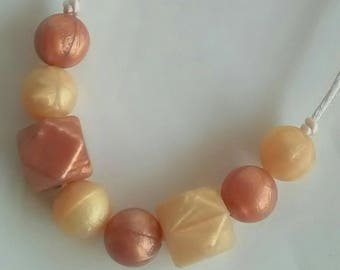 Lovely rose gold and gold round and hexagon beads on a nylon cord with breakaway clasp.