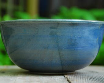 Handmade, thrown, and turned stoneware bowl. Blue decorating slip with transparent green glaze.