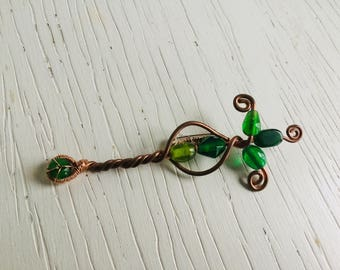 Brooch of copper wire and green glass beads