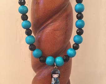 Little girls turquoise cheesewood and black beaded stretch necklace with adorable Geisha Kokeshi doll charm