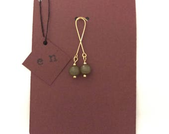 Gold dangle earrings with a single Olive Green bead