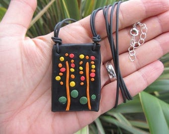 pendant necklace table from polymer clay theme yellow-orange flowers on black rubber cord