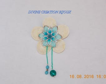 A flower brooch and its light blue beads and green chandelier