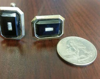 Rectangle gold tone cuff links with black center.