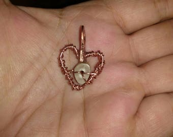 Copper wire heart pendant with a tear drop suspended in the middle