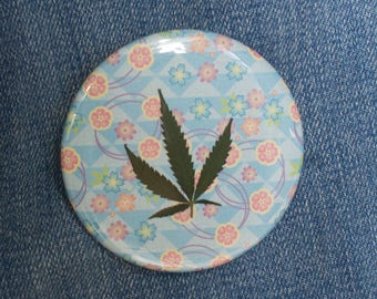Pressed Cannabis Leaf Button on Blue, Pink & Purple Background