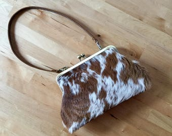 Brown and White cowhide clutch with strap. antique gold frame, hair on hide bag