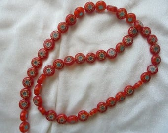 Bead, millefiori glass, 7mm red flat coin with flower design, sold per 16 inch strand. There are 50 beads on the strand.