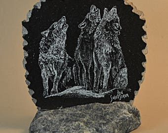 Trio of howling wolves hand etched on black granite