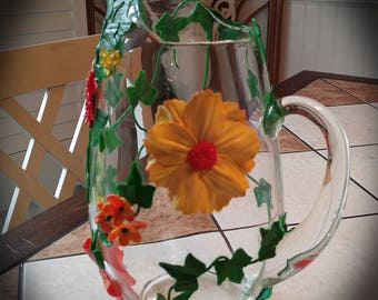 beautifulglass art pitcher with yellow and orange flowers and ivy.