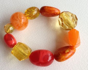 Bracelet  - pretty  plastic beaded elasticated bracelet yellow large pebble shaped bead and faceted lucite