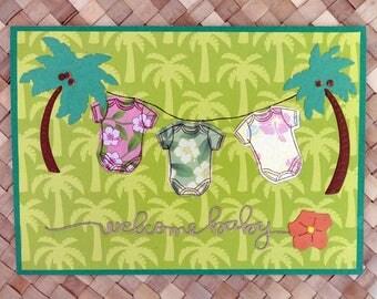 Welcome baby card with Hawaiian onesies on coconut tree clothesline v. 1