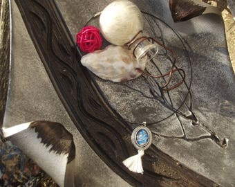 "Necklace black cord with silver charm, oval glass cabochon with print ""paint stains"" and white tassel."