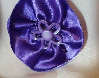 Purple round satin rosette hair barrette. Accented with a purple flower button.