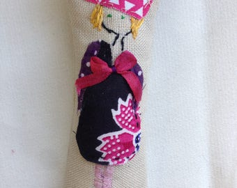Doll brooch embroidered with a story