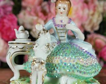upcycling Design, porcelain figurine in Rococo style of lady with a little dog on her lap, Marie Antoinette dress full of crystals