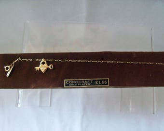Dainty Corocraft Vintage Gold Plated bracelet with heart padlock and key charm on figaro chain on display card
