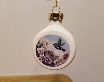 Ceramic Hummingbird with Purple flowers on blue background decal fired on clear glazed Ornament (#935)